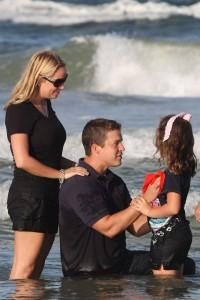 Pastorul Isaac Hunter cu soția, botezându-și fiica. Pastorul, în vârstă de 36 de ani și tată a trei copii, a recunoscut o relație ilicită cu o membră a bisericii și a fost acuzat de soția sa de violență domestică.